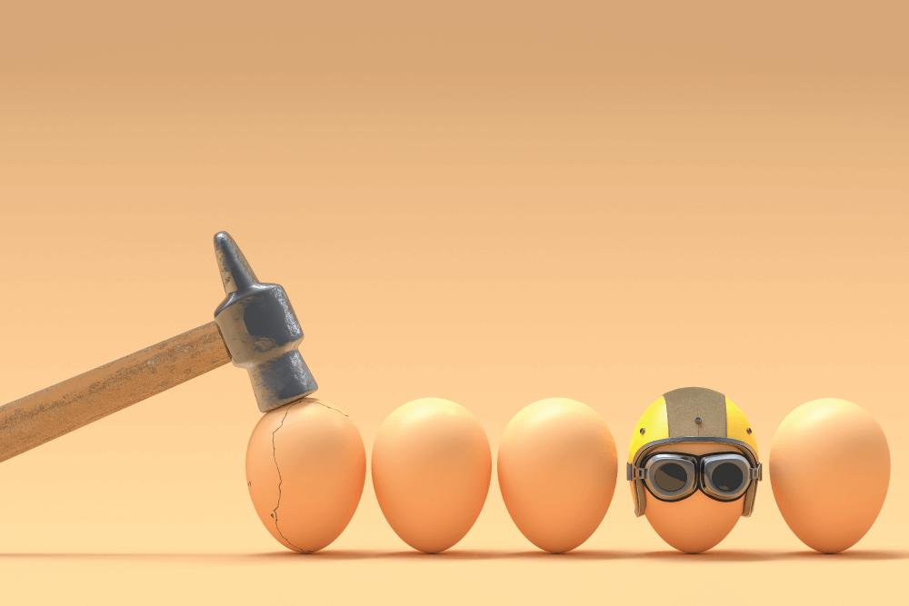uma martelo está quebrando ovos, mas um deles está usando um capacete